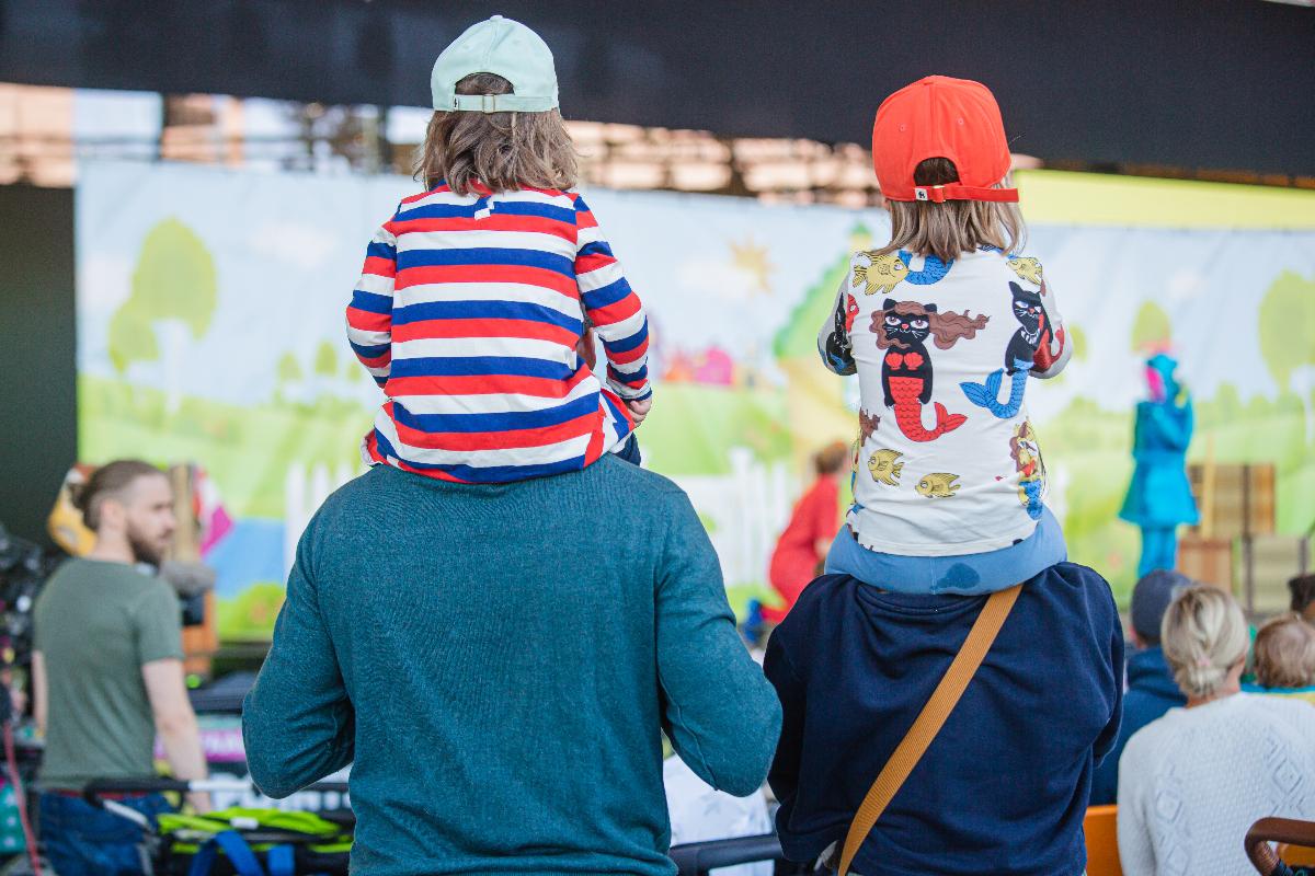 Lapsia istumassa aikuisten hartioilla katsoen konserttia.