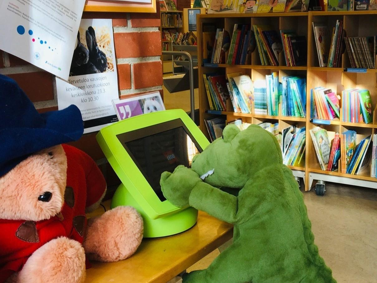 Vihreä pehmodinosaurus istuu kirjastossa lastenosastolla, pöydällä on vieressä suuri pehmolelunalle yllään punainen takki ja sininen hattu. Taustalla on kirjahyllyjä, joissa on lasten kuvakirjoja. NC.