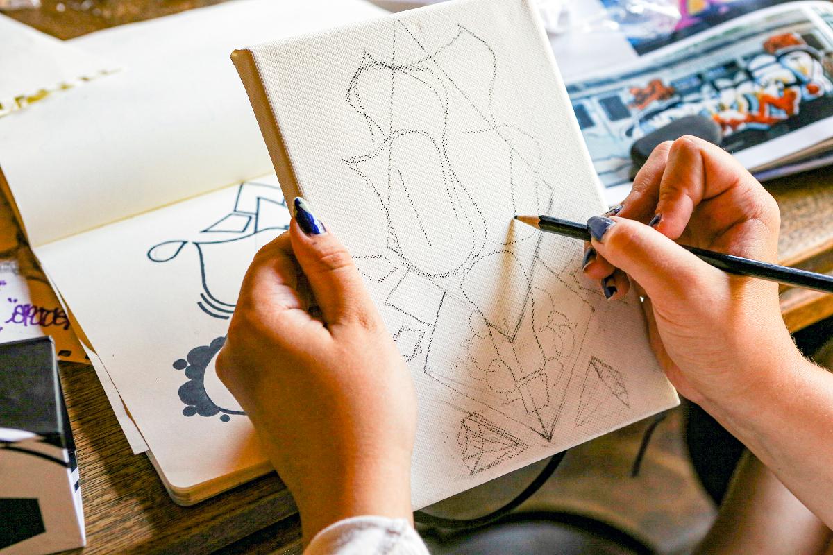 Kuvassa näkyy kädet luonnostelemassa piirustusta